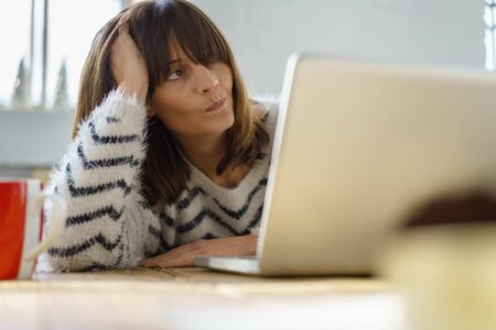 wry: Puzzled woman staring up into the air with a grimace and wry look as she ponders a problem while leaning on her elbow seated at a laptop computer