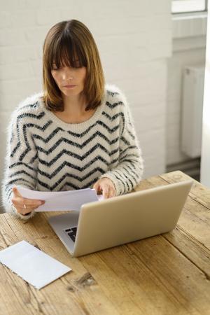 papier a lettre: Femme lisant une lettre ouverte avec une enveloppe blanche sur la table avec un regard sérieux comme elle se repose travailler sur un ordinateur portable à la maison Banque d'images