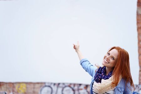 adult wall: Beautiful young smiling female adult in red hair and scarf pointing to white area on wall
