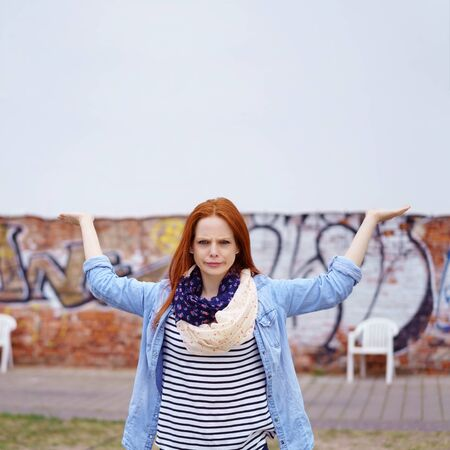 extends: Woman with blue and lacy scarf extends arms in front of large blank wall