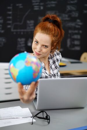international: Single confident European woman in red hair holding globe in classroom with obscured chalkboard background Stock Photo