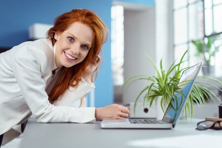 Gorgeous woman leaning toward laptop computer on desk with plant beside it in small office