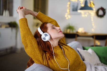 Calm woman in yellow sweater and red hair with eyes close stretching with earphones