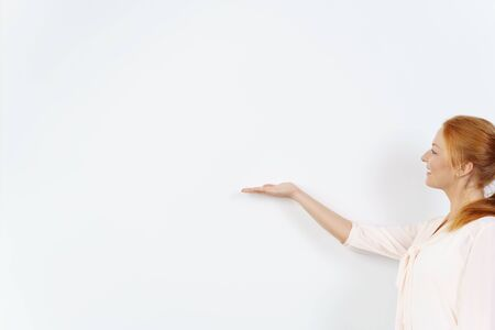 extends: One woman in a pretty blouse and with red hair extends hand with palm side up against a blank white board Stock Photo