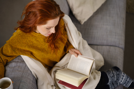 Pretty young woman relaxing reading a book on a comfortable sofa at home wrapped in a blanket with a cup of hot tea, high angle view