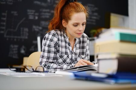 red hair girl: Calm student reviewing work at desk in classroom with stack of books and pair of eyeglasses in foreground Stock Photo