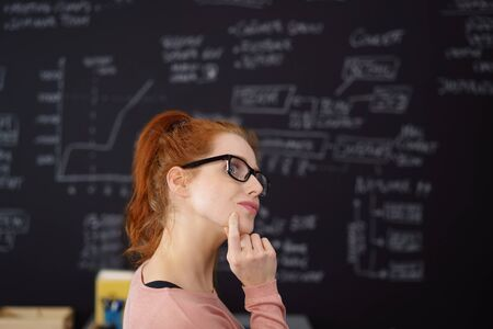 inscribed: Side portrait of red haired woman in glasses thoughtfully standing against inscribed blackboard holding finger to her chin