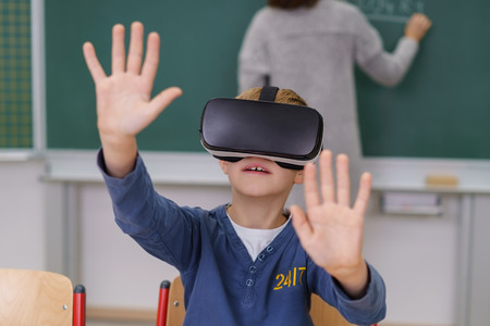 Little boy sitting in classroom wearing virtual reality helmet with arms stretched forward and palms up, groping something invisible Stock Photo