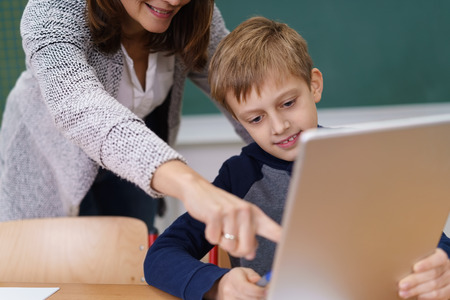 one child: Teacher pointing out something on a tablet computer to a young student in the classroom as he sits at his desk