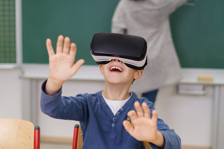 interacts: Happy young schoolboy wearing VR goggles or headset grinning and gesturing with his hands as he interacts with his virtual environment Stock Photo