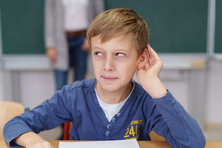 Young boy in a classroom putting his hand to his ear while rolling his eyes and looking away