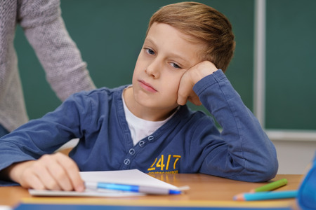 Bored young schoolboy sitting in class with his head resting on his hand looking to the side oblivious to his teacher approaching from behind Stock Photo