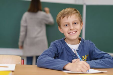 school work: Happy little boy doing class work in school sitting at his desk writing notes and grinning at the camera