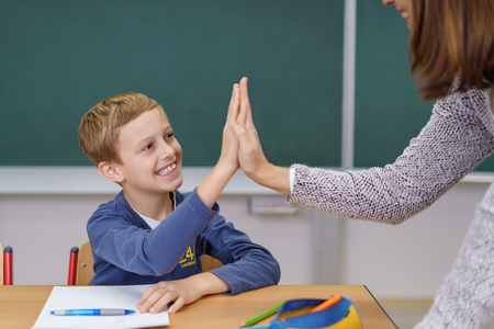 Teacher and happy grinning young student doing a high fives as the schoolboy finally succeeds in understanding something