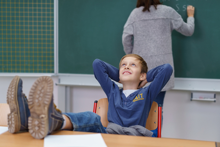 Naughty young schoolboy with his feet up on the desk looking up into the air with a confident grin as the teacher works in the background