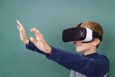 Little boy standing against green chalkboard wearing virtual reality 3D helmet stretching arms forward and groping something with his hands Stock Photo