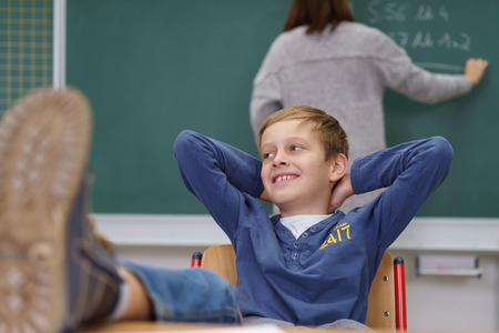 boy kid: Young boy with his feet up on the desk and a mischievous grin sitting in the classroom as the teacher writes on the blackboard with her back to him