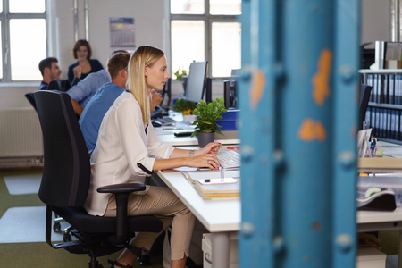 computer office: Side view of young woman work among colleagues in open space office, with blue metal pillar in soft focus in foreground