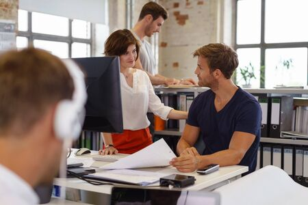 casual office: Young people in casual clothes woman and man in office environment talking to each other