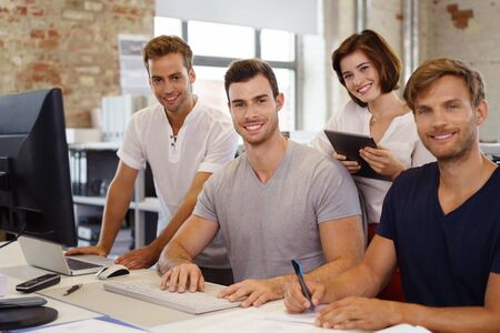 Four young people, three men and woman smiling at camera, while working together in office Stock Photo