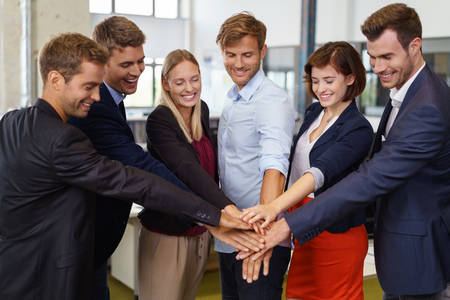 jubilation: Team of business colleagues putting hands crossed together showing unity, smiling and celebrating Stock Photo