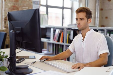 Young man in casual white shirt working in office intently looking at computer screen Stock Photo