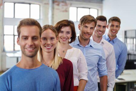 personas de pie: Jóvenes sonriendo mientras posando a la cámara de pie en cascada fila detrás de sí en la oficina, vistiendo ropa casual Foto de archivo