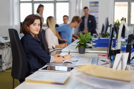 Friendly young businesswoman pausing to look at the camera with a quiet smile as she works at her desk in a large busy open plan office with young colleagues