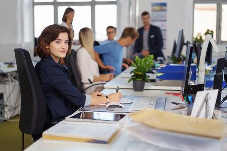 Freundliche junge Geschäftsfrau Pausieren in die Kamera mit einem ruhigen Lächeln zu sehen, wie sie in einem großen beschäftigt offene Büro mit jungen Kollegen an ihrem Schreibtisch arbeitet Standard-Bild - 70547126