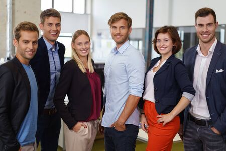 businesspeople: Team of young businesspeople in casual clothes standing close and posing to camera smiling