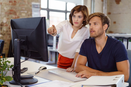 Woman showing something to young man colleague pointing her finger to computer screen, both looking at monitor