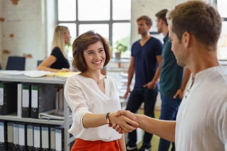 Piuttosto giovane donna sorridente mentre saluto uomo con la stretta di mano, in piedi in ambiente di ufficio con altre persone in background soft focus Archivio Fotografico