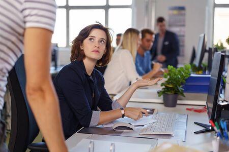 sad look: Pareja de negocios en una discusión seria con un colega haciendo un gesto hacia su ordenador con la mano en una oficina de planta abierta ocupada
