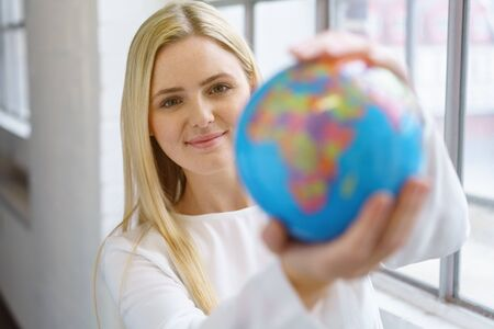 show window: Pretty young blonde woman in white blouse looking at small globe in her hands blurred in the foreground