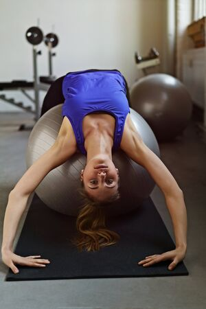 facing backwards: Fit supple young woman doing pilates exercises bending backwards over a gym ball with her hands touching the floor facing the camera in a health and fitness concept