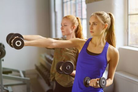emotionless: Two young woman in sportswear doing exercise with dumbbells in gym, looking away emotionless while standing with arm stretched out over big window background