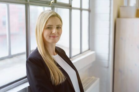 Friendly businesswoman enjoying a break at the office standing leaning against a large window smiling at the camera