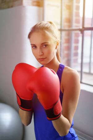 emotionless: Portrait of attractive female boxer in red gloves holding hands to her face, looking at camera emotionless while standing in gym over big window