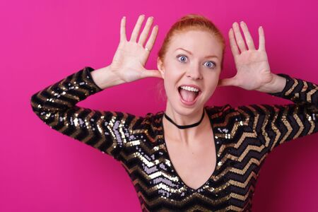funny face: Woman makes faces with hands at her ears while wearing shiny black and gold blouse