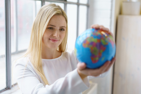 selects: Pretty young blond woman planning her summer vacation standing in front of a bright window holding a world globe as she selects her destinations