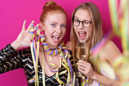 red hair girl: Vivacious young girl friends celebrating together at a party wearing colorful streamers and drinking champagne as they laugh at the camera Stock Photo