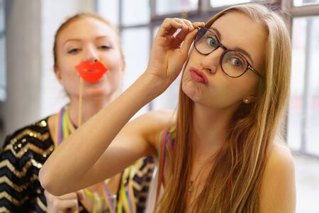 puckering lips: Two playful young women goofing around, with one puckering up her lips for a kiss and the other using a photo booth red lip accessory as they party together with streamers