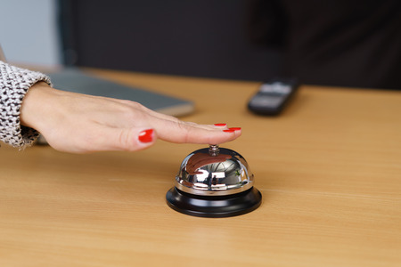 Woman requesting assistance at a hotel reception desk ringing the silver service bell on the wooden counter, close up of her hand Stock Photo