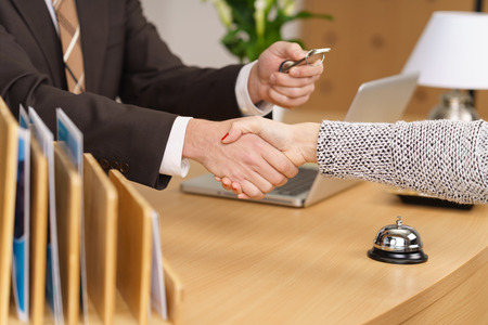 over the counter: Front desk manager at a hotel greeting a client shaking her hand across the counter as he hands over a door key on a fob Stock Photo