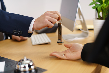 Manager or reception at a hotel handing over a room door key across the front desk to a customer