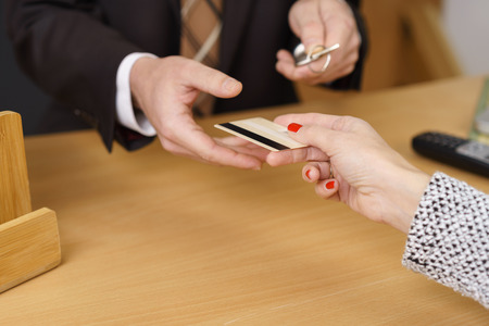 over the counter: Woman paying her hotel bill by credit card handing it over the counter to the manager or receptionist as he holds the door key Stock Photo