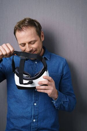 visualizing: Smiling young man in blue shirt looking at virtual reality 3D glasses in his hands standing against grey wall background