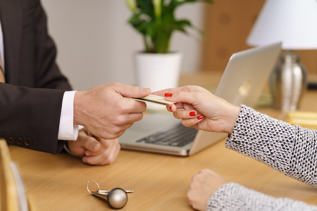 settling: Woman settling her hotel bill with a bank card handing it to the male receptionist with her door key lying on the counter, close up of their hands Stock Photo