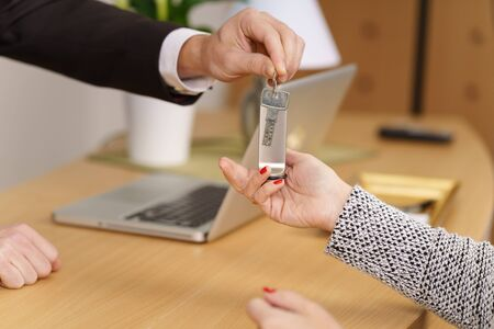 Receptionist handing a female customer a door key at a hotel passing it over the wooden counter, close up on their hands Stock Photo