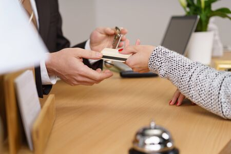 over paying: Woman booking out of a hotel paying by credit card handing it over the front counter to the male receptionist Stock Photo